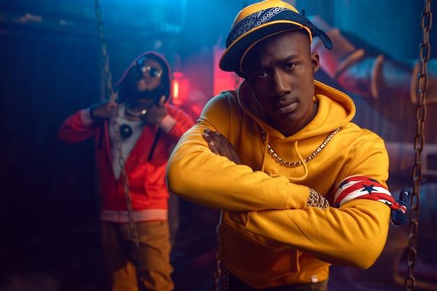 Dwóch stylowych raperów, tańczących breakdance z fajną undergroundową dekoracją. wykonawcy hip-hopu, modni rapujący, breakdance