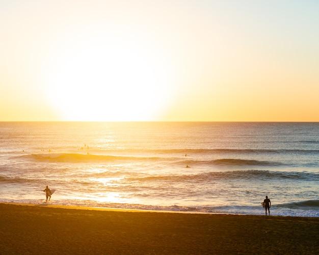 Dwóch surferów płci męskiej na plaży z deską surfingową w drodze do wody, aby surfować o wschodzie słońca