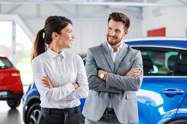 Dwóch sympatycznych, uśmiechniętych, odnoszących sukcesy sprzedawców samochodów, stojących z rękami skrzyżowanymi w salonie samochodowym i patrzących na siebie.