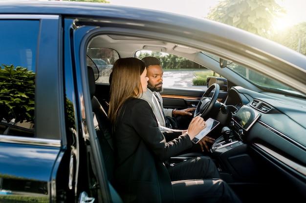 Dwóch szczęśliwych biznesmenów, afrykańskiego mężczyzny i kobiety rasy białej, za pomocą cyfrowego tabletu z urządzeniami elektronicznymi siedząc w czarnym samochodzie