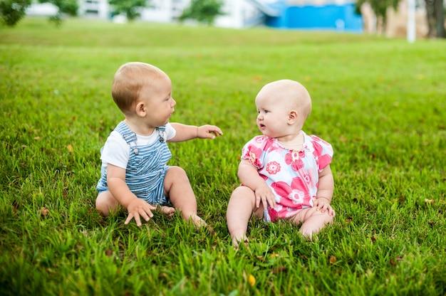 Dwóch szczęśliwych chłopców i dziewczynka w wieku 9 miesięcy, siedzących na trawie i wchodzących w interakcje, rozmawiających, patrzących na siebie.