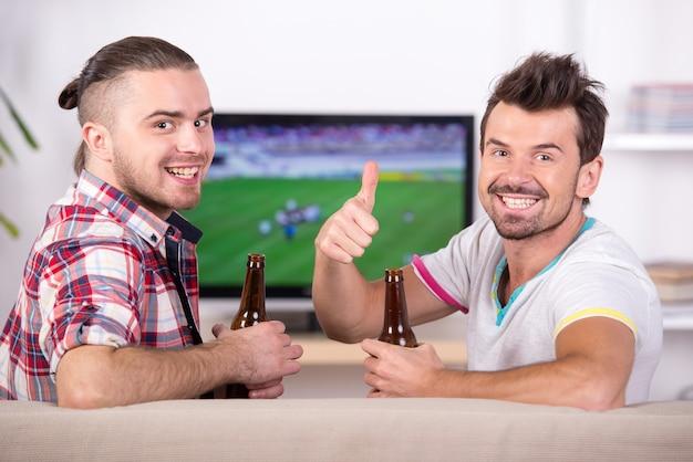 Dwóch szczęśliwych fanów piłki nożnej podczas oglądania ulubionej drużyny w telewizji.