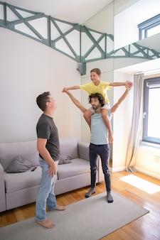 Dwóch szczęśliwych homoseksualnych ojców i syn bawią się w domu, chłopiec jedzie na szyi mężczyzny i się śmieje. pełna długość. pojęcie rodziny i rodzicielstwa