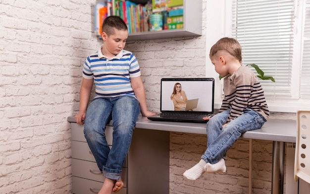 Dwóch szczęśliwych małych przyjaciół. chłopcy korzystający z inteligentnego cyfrowego tabletu w domu.