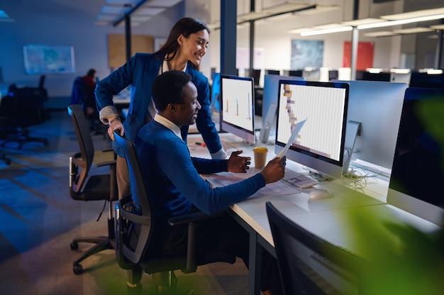 Dwóch szczęśliwych menedżerów pracujących w biurze nocnym. pracowników płci męskiej i żeńskiej, ciemne wnętrze centrum biznesowego, nowoczesne miejsce pracy