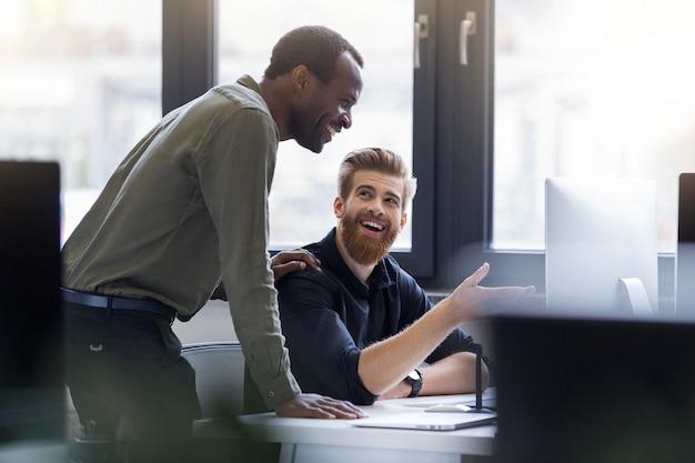 Dwóch szczęśliwych mężczyzn pracujących razem nad nowym projektem biznesowym