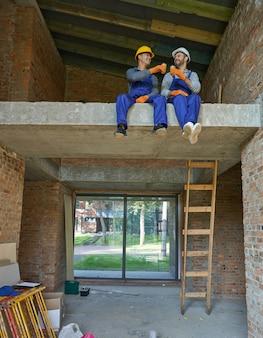 Dwóch szczęśliwych młodych budowniczych w niebieskich kombinezonach i twardych kapeluszach odpoczywających, siedzących na betonowej podłodze, pijących kawę podczas pracy przy budowie domu