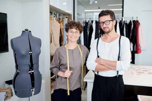 Dwóch szczęśliwych młodych kreatywnych projektantów odzieży stojącej przy manekinie podczas pracy w swoim studio