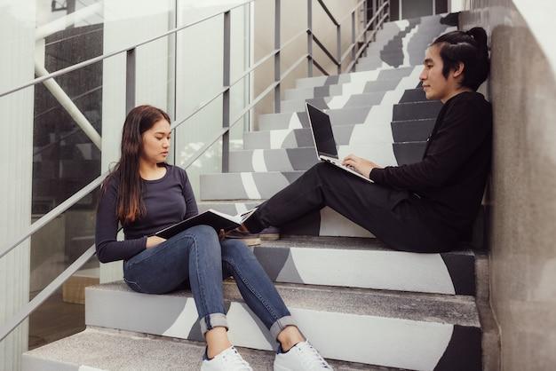 Dwóch szczęśliwych nastoletnich studentów studiujących pracę domową z zeszytu, siedząc na schodach na zewnątrz.