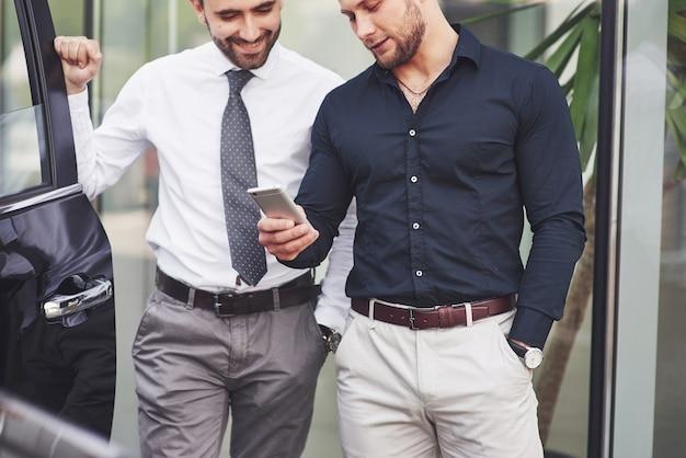 Dwóch szczęśliwych, pewnych siebie młodych biznesmenów stojących przy biurze.