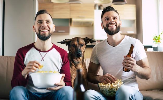 Dwóch szczęśliwych podekscytowanych brodatych przyjaciół oglądających telewizję lub mecz sportowy z psem, siedząc na kanapie w domu w weekend