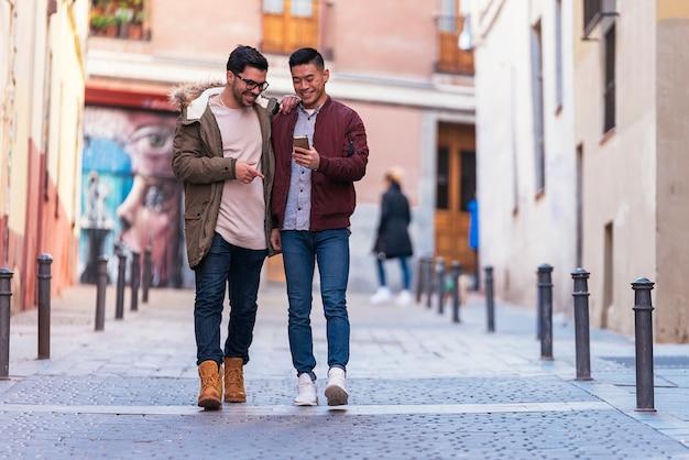 Dwóch szczęśliwych przyjaciół korzystających z telefonu komórkowego na ulicy. koncepcja przyjaźni.