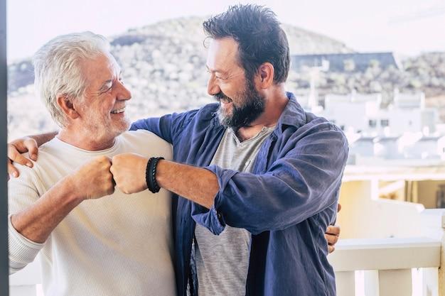 Dwóch szczęśliwych przyjaciół płci męskiej, ojciec i syn, dobrze się razem bawią, dając sobie przyjacielski cios