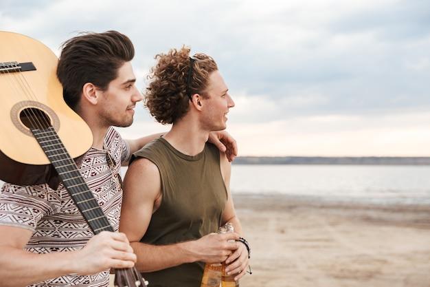 Dwóch Szczęśliwych Przyjaciół Płci Męskiej Spacerujących Po Plaży, Niosących Gitarę Premium Zdjęcia
