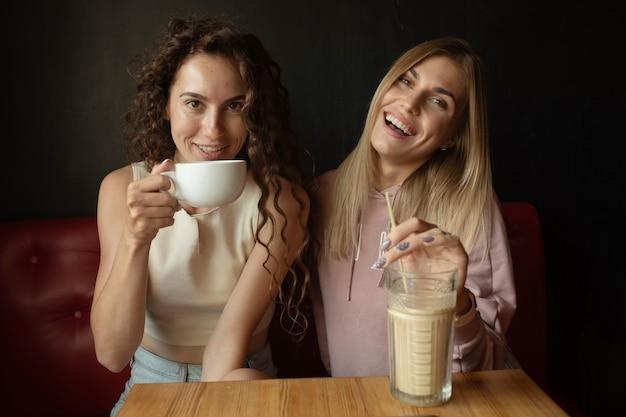 Dwóch szczęśliwych przyjaciół rozmawiających przy rozmowie w kawiarni