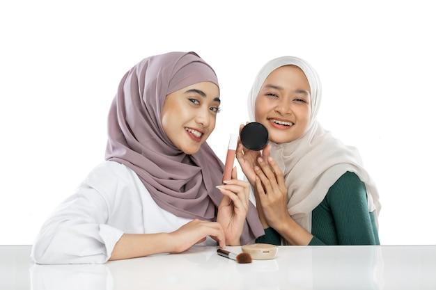 Dwóch szczęśliwych, przyjaznych vlogerów z zawoalowaną dziewczyną, trzymających kosmetyki do makijażu, tworzących wideo vlog