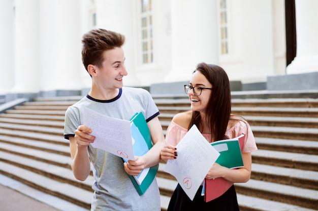 Dwóch szczęśliwych uczniów otrzymało doskonały wynik testu końcowego, patrzą na siebie i nie mogą uwierzyć własnym oczom, że mają najwyższą ocenę a