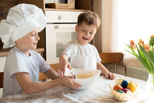 Dwóch szczęśliwych wesołych chłopców robi ciasto na wielkanocny tort w domu w kuchni