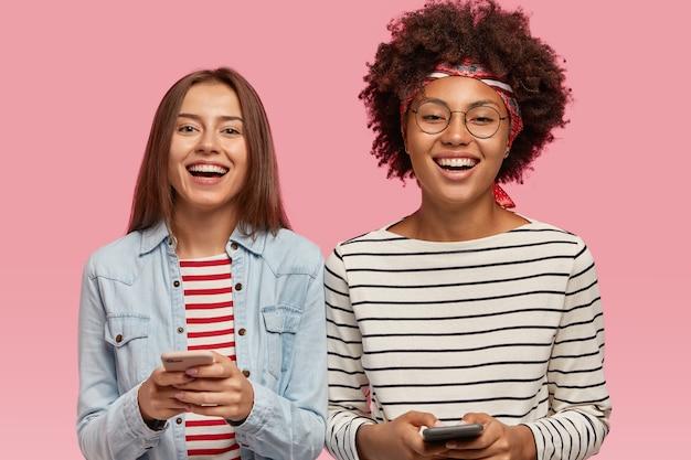 Dwóch szczęśliwych, wieloetnicznych przyjaciół trzyma w rękach nowoczesny telefon komórkowy, śmieje się i dobrze się bawi, trzyma nowoczesne telefony komórkowe, komunikuje się online
