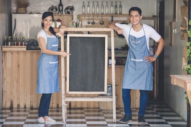 Dwóch szczęśliwych właścicieli małych firm gotowych do otwarcia kawiarni