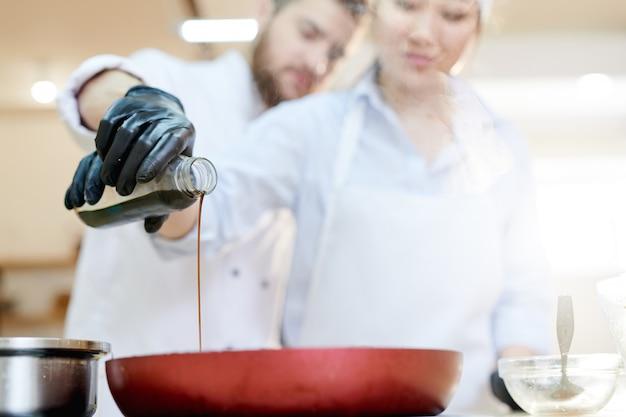 Dwóch Szefów Kuchni Leje Sos Sojowy Premium Zdjęcia
