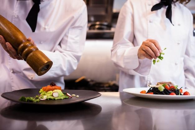 Dwóch szefów kuchni, ozdabiając posiłek na blacie