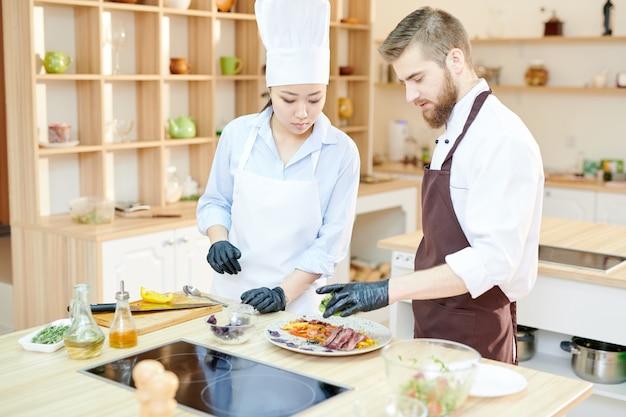Dwóch szefów kuchni pracujących nad potrawami