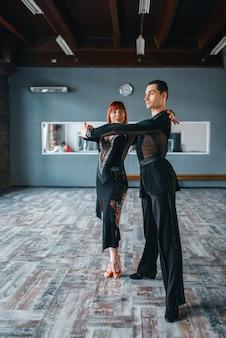 Dwóch tancerzy elegancji w kostiumach na treningu tańca towarzyskiego w klasie. partnerki płci żeńskiej i męskiej w profesjonalnym tańcu parowym w studio