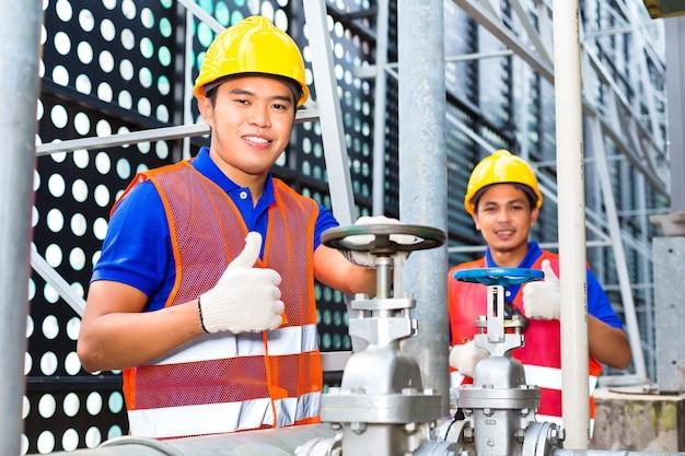 Dwóch techników lub inżynierów pracujących przy zaworze w urządzeniach technicznych budynku lub na terenie przemysłowym