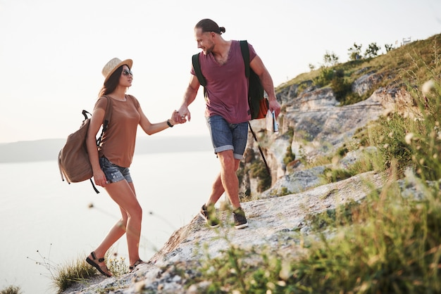 Dwóch turystów mężczyzna i kobieta z plecakami wspiąć się na szczyt góry i cieszyć się wschodem słońca. podróży styl życia przygoda wakacje koncepcja