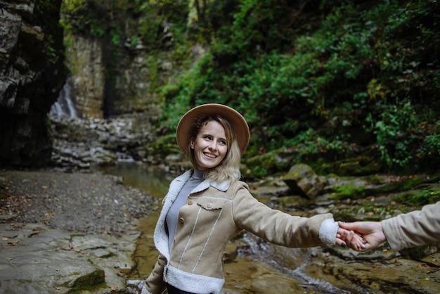 Dwóch turystów na łonie natury. zbliżenie mężczyzny i kobiety, trzymając się za ręce podczas chodzenia ścieżką