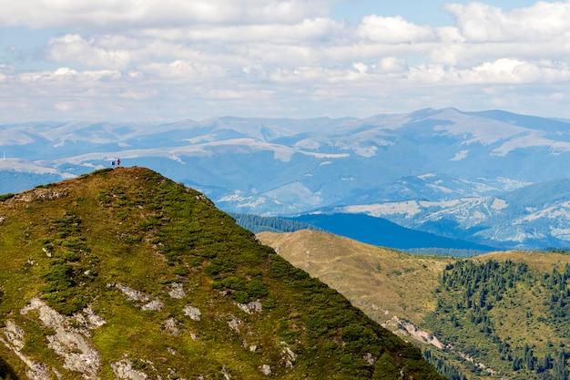Dwóch turystów stojących na ogromnym górskim klifie. turystyka piesza. koncepcja siły natury.