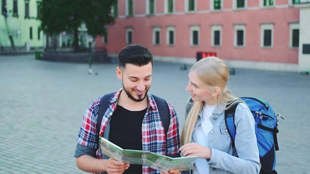 Dwóch turystów z mapą szukających nowego historycznego miejsca w centrum miasta