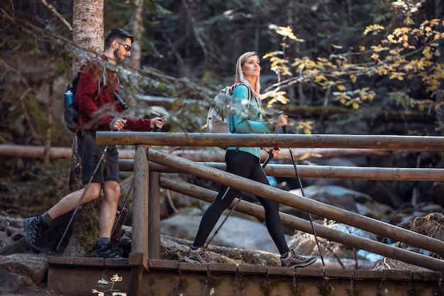 Dwóch turystów z plecakiem chodzących po drewnianym moście, patrząc na krajobraz w lesie.