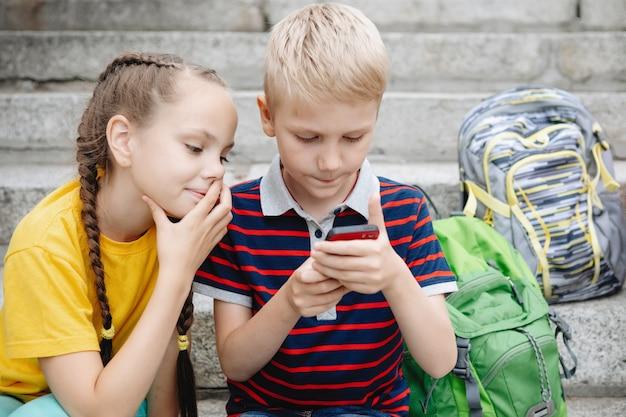 Dwóch uczniów, chłopiec i dziewczynka siedzą na schodach i patrzą na smartfona.