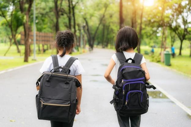Dwóch uczniów chodzących do szkoły podstawowej chodzi do szkoły.