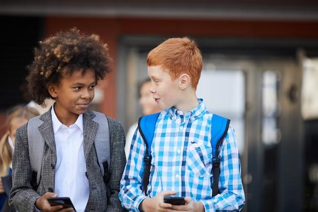Dwóch uczniów z telefonami komórkowymi
