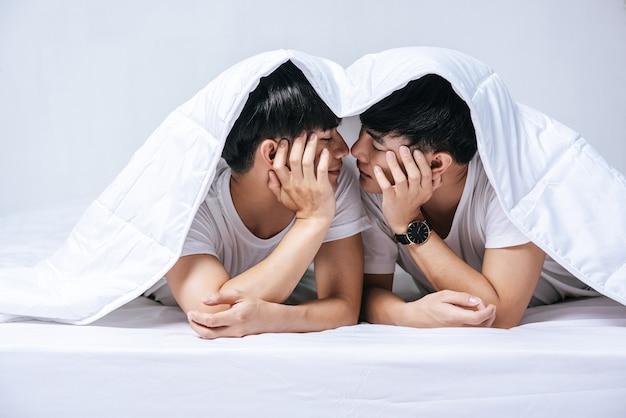 Dwóch ukochanych młodych mężczyzn spało razem w łóżku.