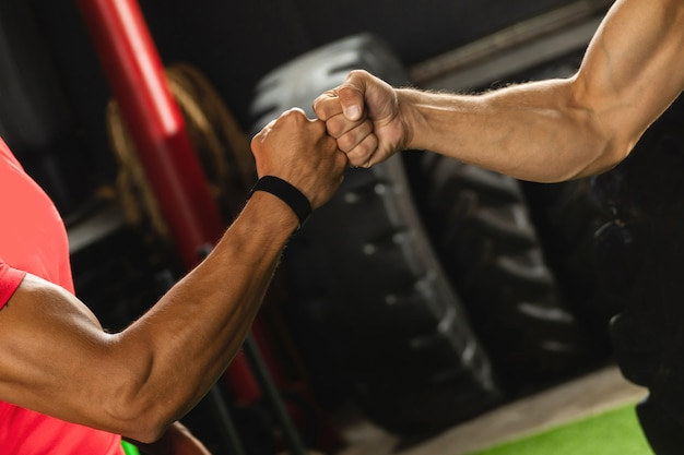 Dwóch umięśnionych mężczyzn robi gest pięści podczas treningu na siłowni