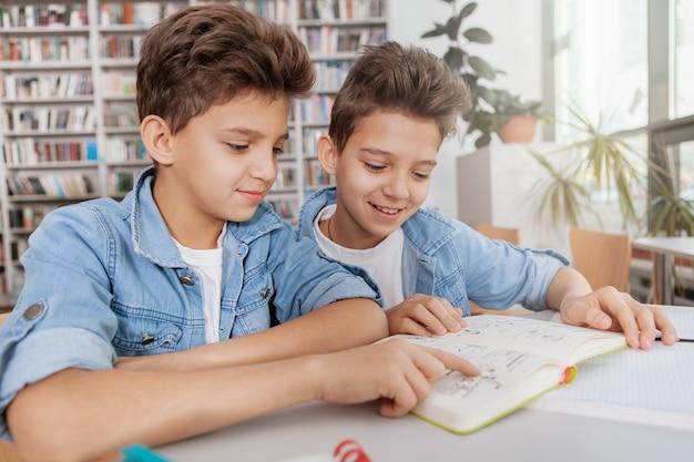 Dwóch uroczych bliźniaków czytających razem książkę w bibliotece