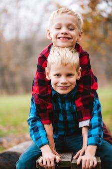 Dwóch uroczych braci chłopców w wieku szkoły podstawowej, 6-7 lat, siedzą na drewnianej ławce, przytulają się w podobnych kraciastych koszulach na tle jesiennego parku