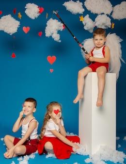 Dwóch uroczych chłopców i dziewczynka aniołów na walentynki