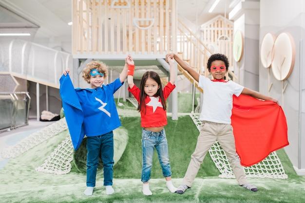 Dwóch uroczych chłopców międzykulturowych w kostiumach superbohaterów i śliczna azjatka trzymająca się za ręce na placu zabaw