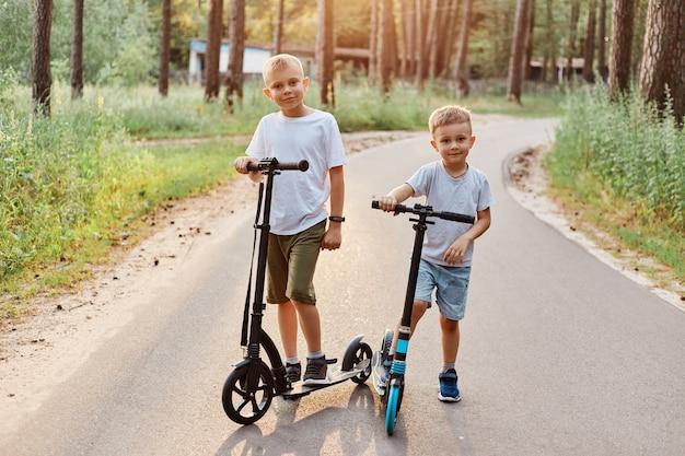 Dwóch uroczych chłopców w koszulkach i szortach w stylu casual, rywalizuje na skuterach, na świeżym powietrzu w parku, w lecie, szczęśliwi bracia spędzają razem czas.