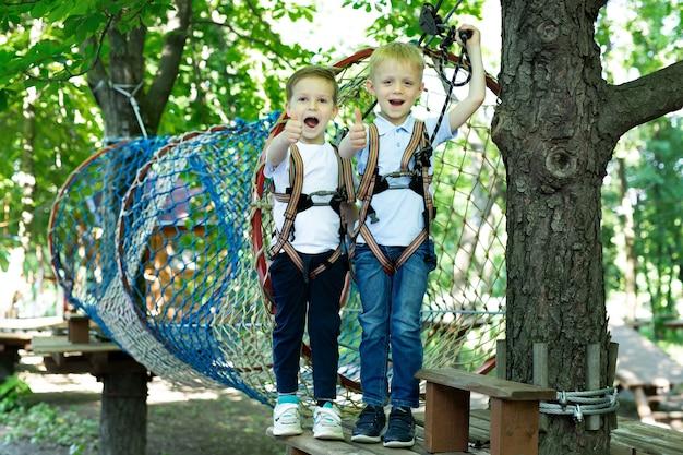 Dwóch uroczych chłopców w parku rozrywki wspina się po skałach lub mija przeszkody na drodze linowej, przytulając się i pokazując kciuki do góry.