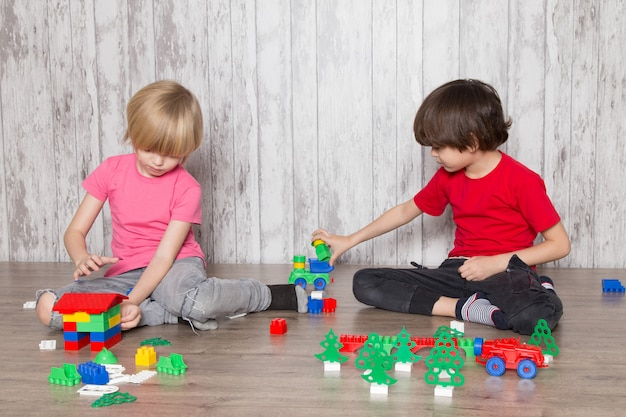 Dwóch uroczych chłopców w różowych i czerwonych koszulkach bawiących się zabawkami
