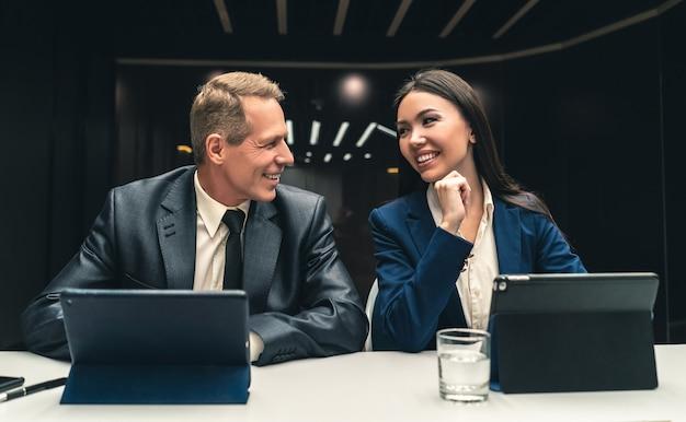 Dwóch uśmiechniętych biznesmenów siedzących przy stole