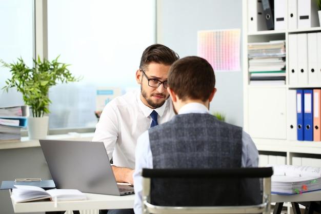 Dwóch uśmiechniętych biznesmenów urzędnik rozważa problem