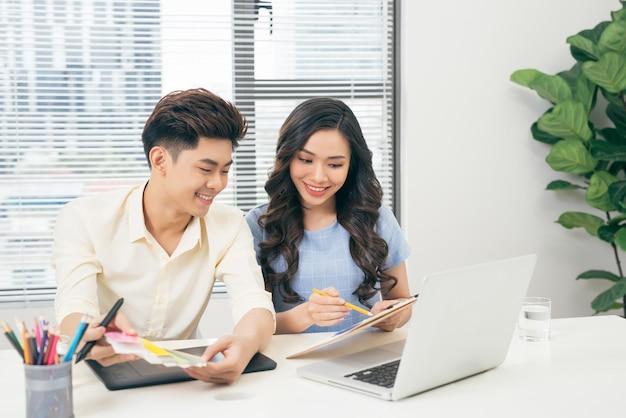 Dwóch uśmiechniętych casualowych projektantów pracujących z laptopem siedząc przy biurku w biurze