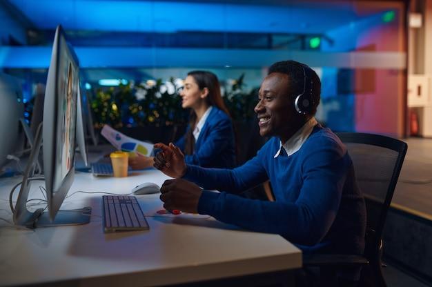 Dwóch uśmiechniętych menedżerów pracuje w nocnym biurze. wesoły pracowników płci męskiej i żeńskiej, ciemne wnętrze centrum biznesowego, nowoczesne miejsce pracy